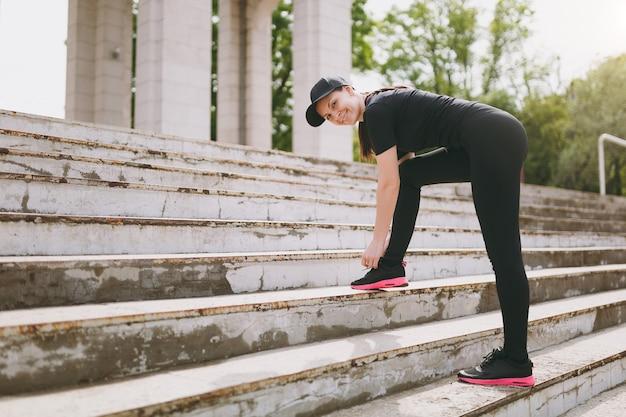Junge lächelnde athletische schöne brünette frau in schwarzer uniform, mütze, die sportübungen macht, aufwärmen vor dem laufen, schnürsenkel auf treppen im stadtpark im freien binden