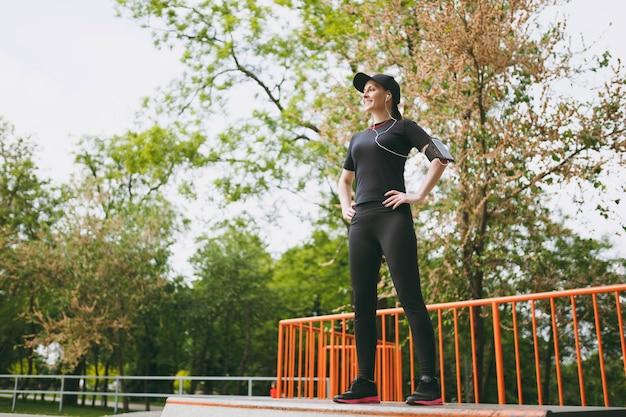 Junge lächelnde athletische schöne brünette frau in schwarzer uniform, mütze mit kopfhörern, die sportübungen macht, aufwärmen vor dem laufen, draußen im stadtpark stehen
