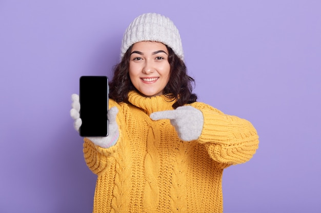 Junge lächelnde attraktive frau, die auf leeren bildschirm des telefons in ihrer hand zeigt