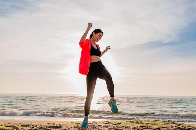 Junge lächelnde attraktive schlanke frau, die sport im morgensonnenaufgang macht, der auf meeresstrand in sportkleidung, gesundem lebensstil springt, musik auf kopfhörern hörend, rosa windjacke tragend, spaß habend