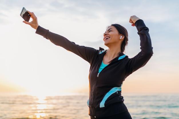 Junge lächelnde attraktive schlanke frau, die sportübungen am morgensonnenaufgangstrand in sportbekleidung, gesundem lebensstil, musik auf kopfhörern hörend macht, selfie-foto auf telefon schauend stark macht