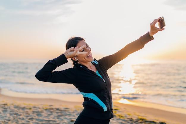 Junge lächelnde attraktive schlanke frau, die sportübungen am morgensonnenaufgangstrand in sportkleidung, gesundem lebensstil, musik auf kopfhörern hörend macht, selfie-foto am telefon in positiver stimmung machend macht
