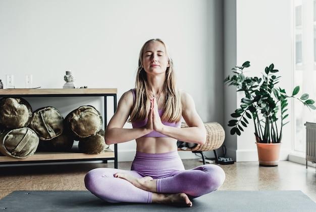 Junge lächelnde attraktive sportfrau, die yoga praktiziert, meditation in lotussitz mit namaste, training, yoga-studio