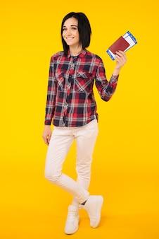 Junge lächelnde aufgeregte studentin, die pass-bordkarten-ticket lokalisiert auf gelbem hintergrund hält.