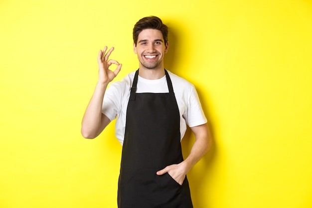 Junge lächelnde barista in schwarzer schürze, die ein okayzeichen zeigt, café oder restaurant empfiehlt, auf gelbem hintergrund stehend