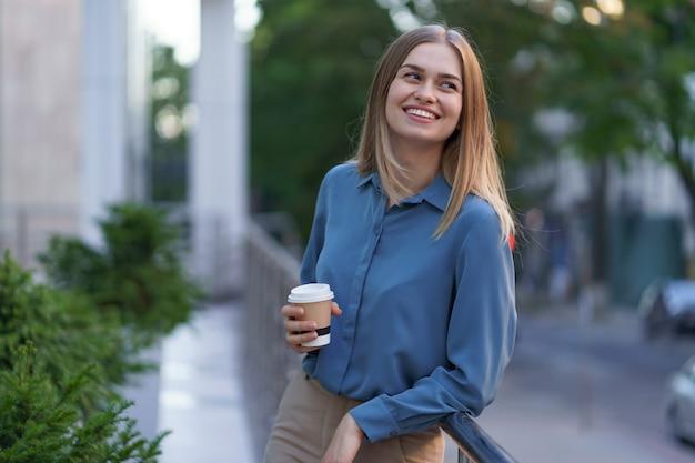 Junge lächelnde berufstätige frau, die eine kaffeepause während ihres vollen arbeitstages hat. sie hält einen pappbecher im freien in der nähe des geschäftsgebäudes, während sie sich entspannt und ihr getränk genießt.