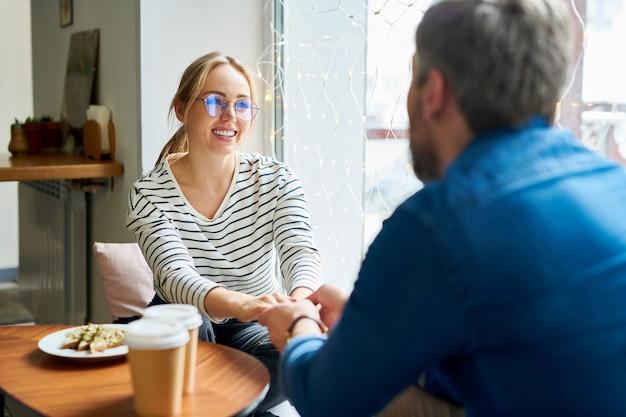 Junge lächelnde blonde frau in der freizeitkleidung, die ihren freund durch hände hält, während beide im café sitzen, getränke und snack haben