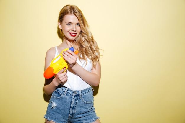 Junge lächelnde blonde frau in der sommerkleidung, die wasserpistole hält
