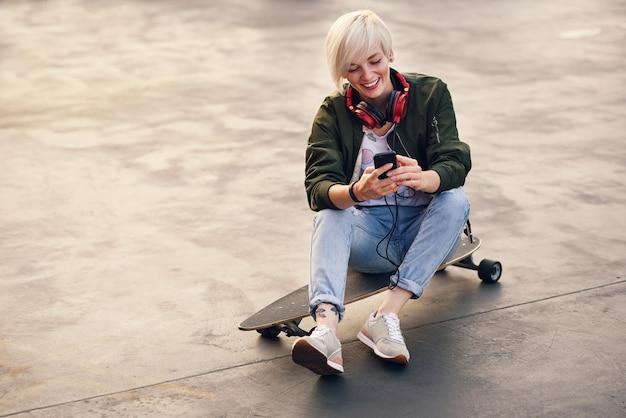 Junge lächelnde blonde frau mit kopfhörern, die telefon beim sitzen auf dem longboard bei sonnenuntergang verwenden.