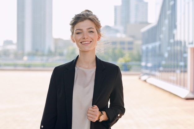 Junge lächelnde blonde geschäftsfrau in formeller kleidung, die vor der kamera gegen das stadtbild mit einer gruppe moderner gebäude steht