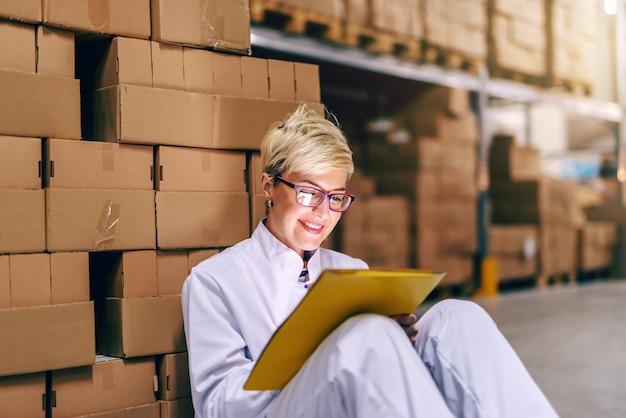 Junge lächelnde blonde kaukasische frau in der weißen uniform und mit brillen, die papierkram beim sitzen auf dem boden im lager tun.