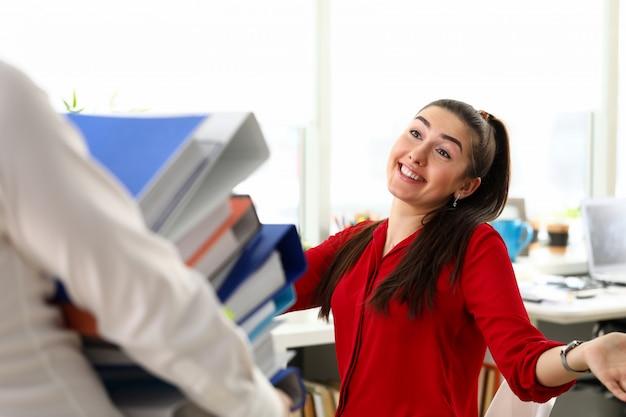 Junge lächelnde brünette frau im roten hemd, das im büro sitzt und kollegen mit haufen von dokumenten begrüßt. geschäftsdame, sekretärin, leute im bürokonzept