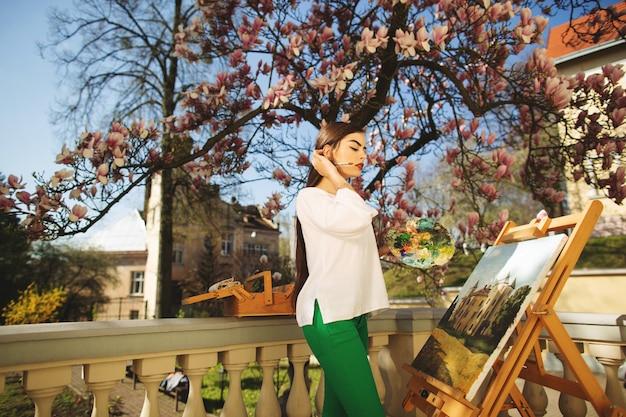 Junge lächelnde brunettekünstlerin malt ein bild auf der straße, nahe einem schönen baum der magnolie