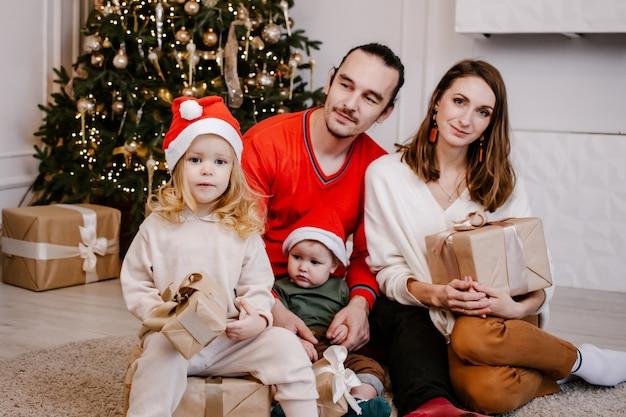 Junge lächelnde eltern geben kindergeschenke an weihnachten, süßes mädchen in der weihnachtsmütze, die kasten in den händen hält.