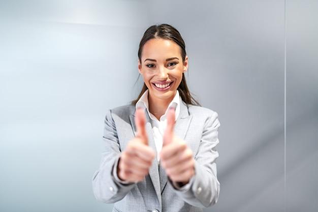 Junge lächelnde erfolgreiche kaukasische geschäftsfrau in der formellen abnutzung, die innerhalb der firmenfirma steht und daumen oben zeigt.