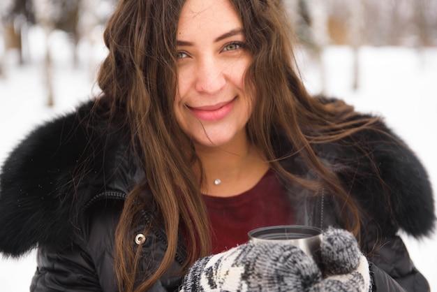 Junge lächelnde frau am schneebedeckten park, der heißes getränk hält