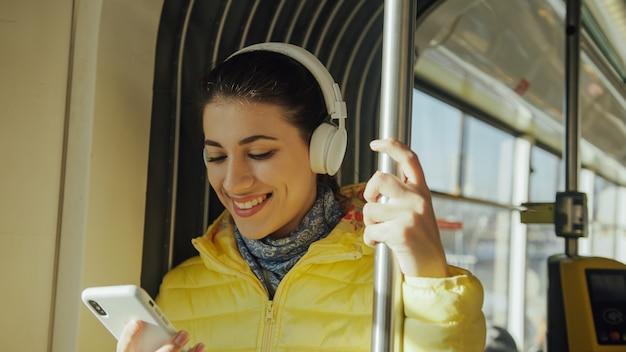 Junge lächelnde frau bei der stellung im zug, in der tram oder im bus. glücklicher weiblicher passagier, der öffentlich musik auf einem transport des smartphone hört. Premium Fotos