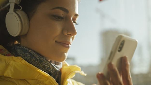 Junge lächelnde frau bei der stellung im zug, in der tram oder im bus. glücklicher weiblicher passagier, der öffentlich musik auf einem transport des smartphone hört.