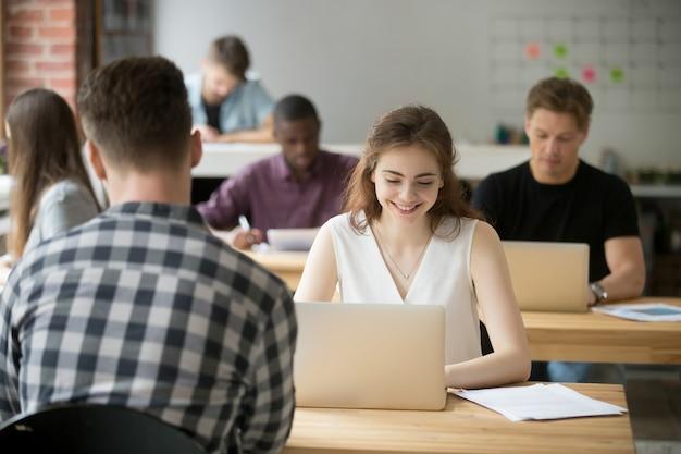 Junge lächelnde frau, die an laptop in coworking büroräumen arbeitet