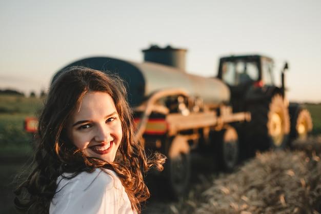 Junge lächelnde frau, die auf feld auf straße mit traktor und feld im sonnenunterganghintergrund steht.