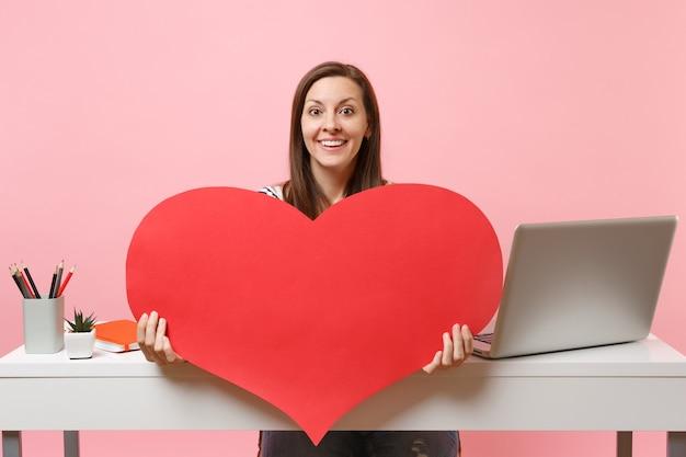 Junge lächelnde frau, die auf kamera rotes leeres leeres herz zeigt, sitzen am weißen schreibtisch mit pc-laptop einzeln auf pastellrosa hintergrund. erfolgsgeschäftskarrierekonzept. kopieren sie platz für werbung.
