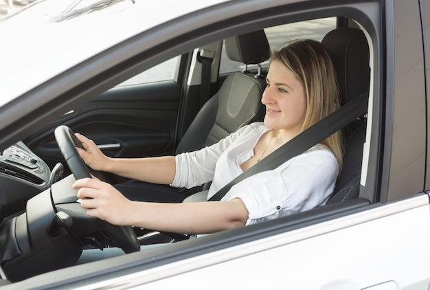 Junge lächelnde frau, die auto fährt und straße betrachtet