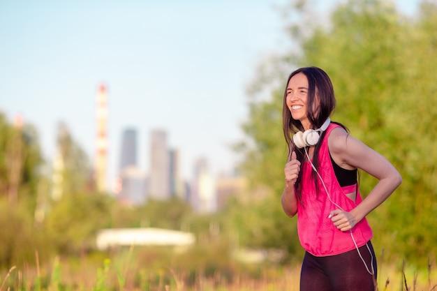Junge lächelnde frau, die draußen sportliche übungen tut
