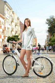 Junge lächelnde frau, die fahrrad auf die straße in der stadt fährt.
