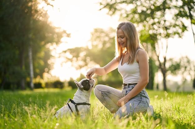 Junge lächelnde frau, die französische bulldogge im park ausbildet