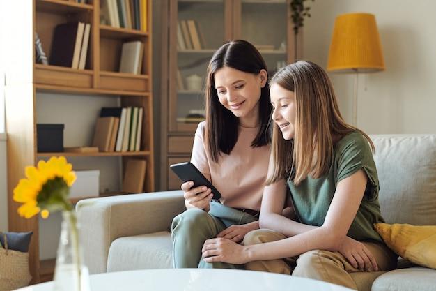 Junge lächelnde frau, die im smartphone durch fotos scrollt, während sie sie ihrer süßen blonden tochter im teenageralter im wohnzimmer zeigt?
