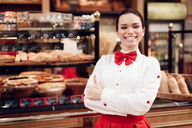 Junge lächelnde frau, die in der modernen bäckerei steht.