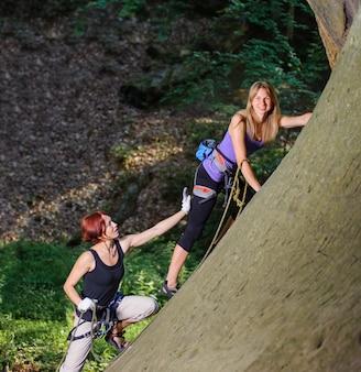 Junge lächelnde frau, die in der natur auf großem flussstein klettert, ihr weiblicher partner, der sie sichert.