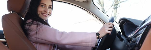 Junge lächelnde frau, die luxusautonahaufnahme fährt