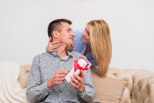 Junge lächelnde frau, die mann mit geschenk auf sofa betrachtet