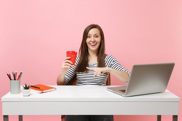 Junge lächelnde frau, die mit dem zeigefinger auf eine tasse kaffee oder tee zeigt, die an einem projekt arbeitet, sitzen im büro mit einem pc-laptop