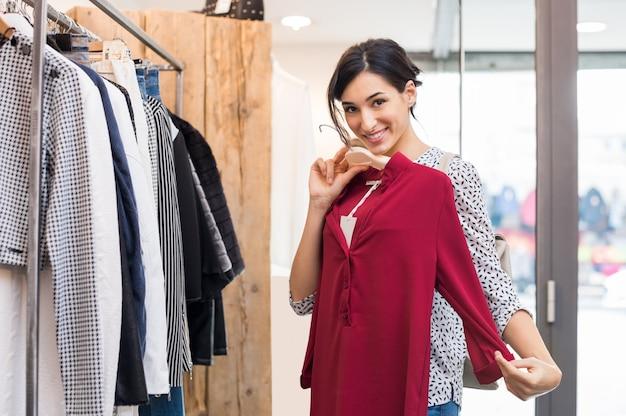Junge lächelnde frau, die neue kleidung im einkaufszentrum versucht