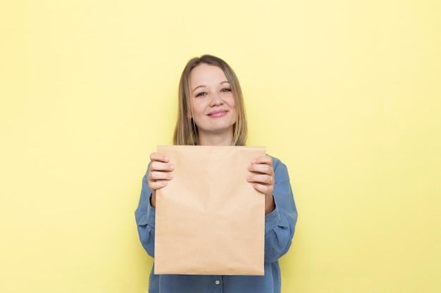 Junge lächelnde frau, die papiertüte in den händen hält. kopieren sie platz für werbung.