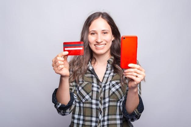 Junge lächelnde frau, die rote kreditkarte und smartphone zeigt.