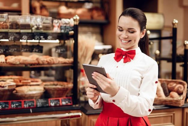 Junge lächelnde frau, die tablet in der modernen bäckerei verwendet