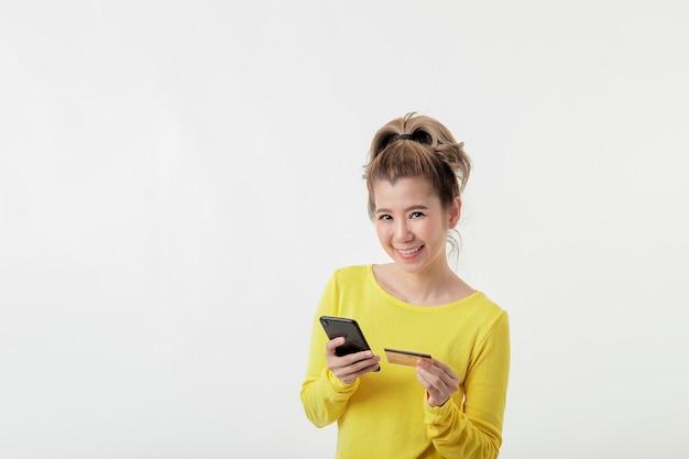 Junge lächelnde frau, die telefon und nummer der kreditkarte verwendet, um online einzukaufen