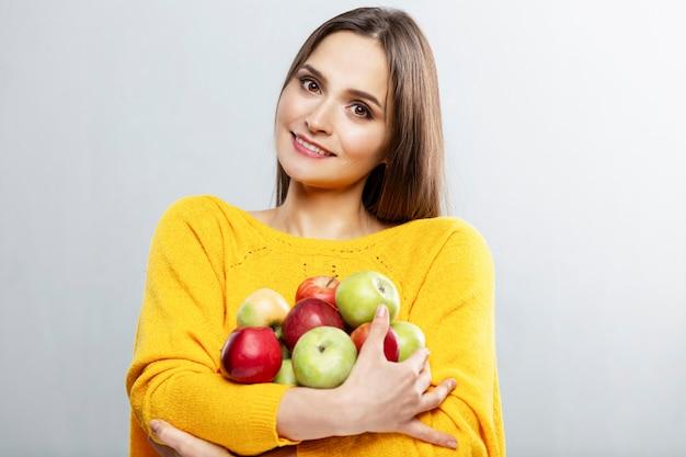 Junge lächelnde frau, die viele rote und grüne äpfel in ihren händen hält. schöne brünette in einem gelben pullover.
