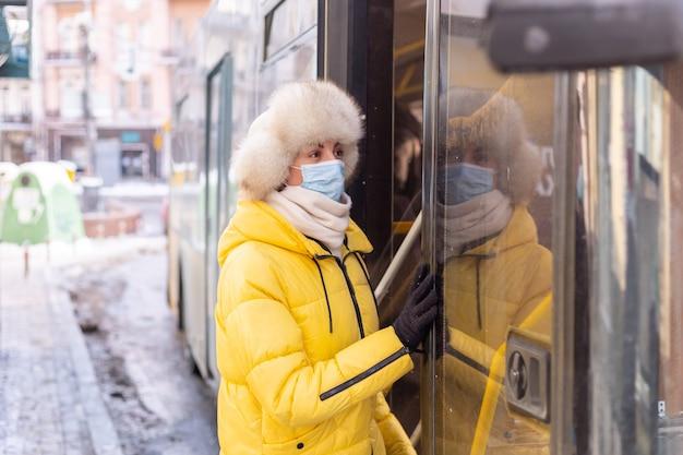 Junge lächelnde frau geht an einem wintertag in den bus
