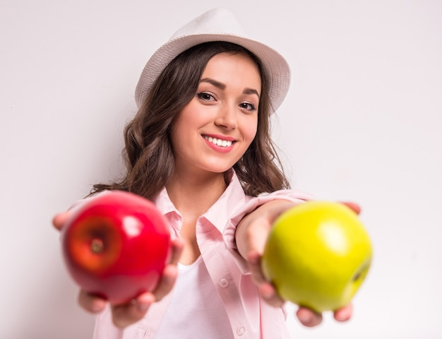 Junge lächelnde frau hält roten und grünen apfel.