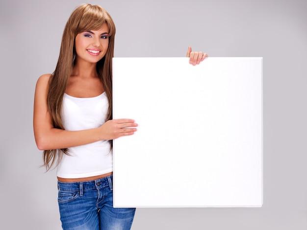 Junge lächelnde frau hält weißes großes banner, das aufwirft