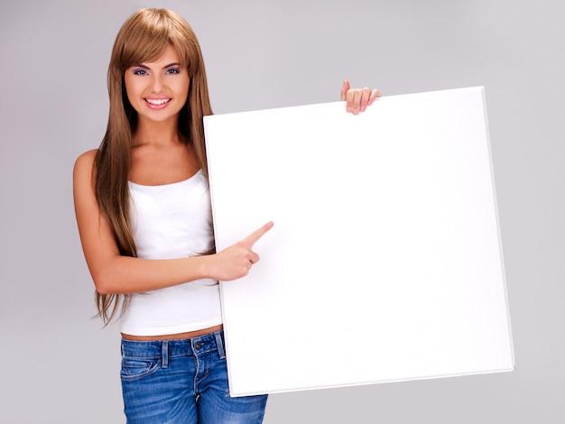 Junge lächelnde frau hält weißes großes plakat und zeigt mit dem finger