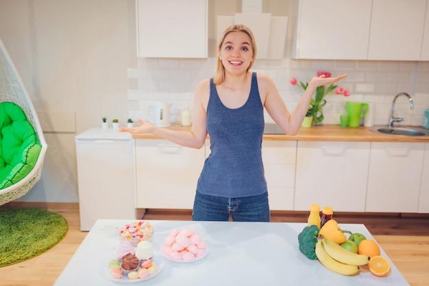 Junge lächelnde frau im blauen t-shirt, das zwischen gesundem und ungesundem essen in der küche wählt