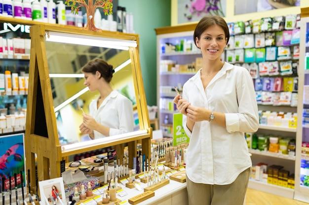 Junge lächelnde frau im kosmetikshop steht nahe bei spiegel mit kosmetikbleistift in ihren händen