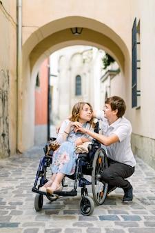 Junge lächelnde frau im rollstuhl und im freudigen mann, die draußen im alten stadtzentrum im sommermorgen gehen