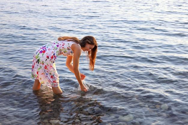 Junge lächelnde frau im sommerkleid steht barfuß im wasser und wäscht ihre hände