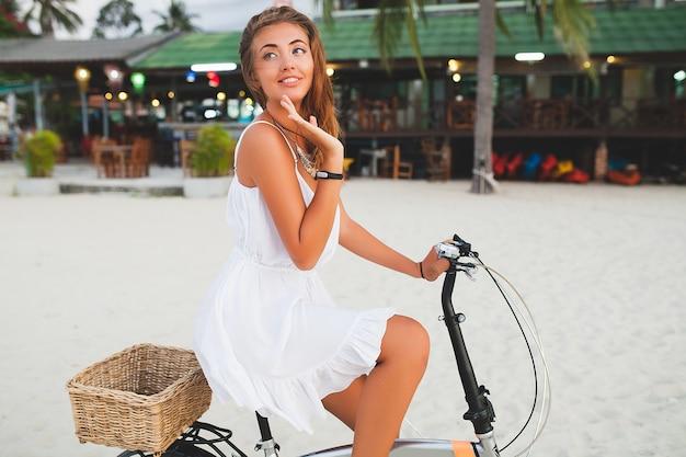 Junge lächelnde frau im weißen kleid, das auf tropischem strand mit fahrrad reist, das auf sommerferien in thailand reist